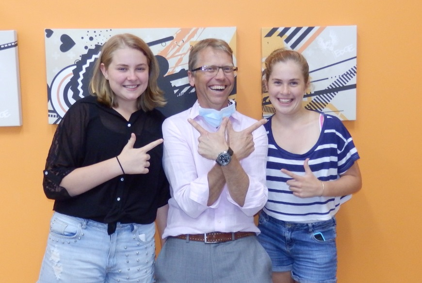 Dr Tod and teenage sisters smile beautifully after removal of braces at ethos orthodontics