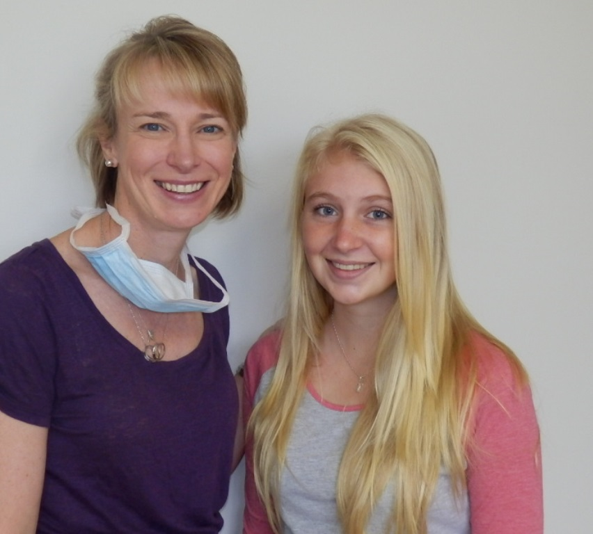 Dr Prove with smiling teenage girl after removing braces