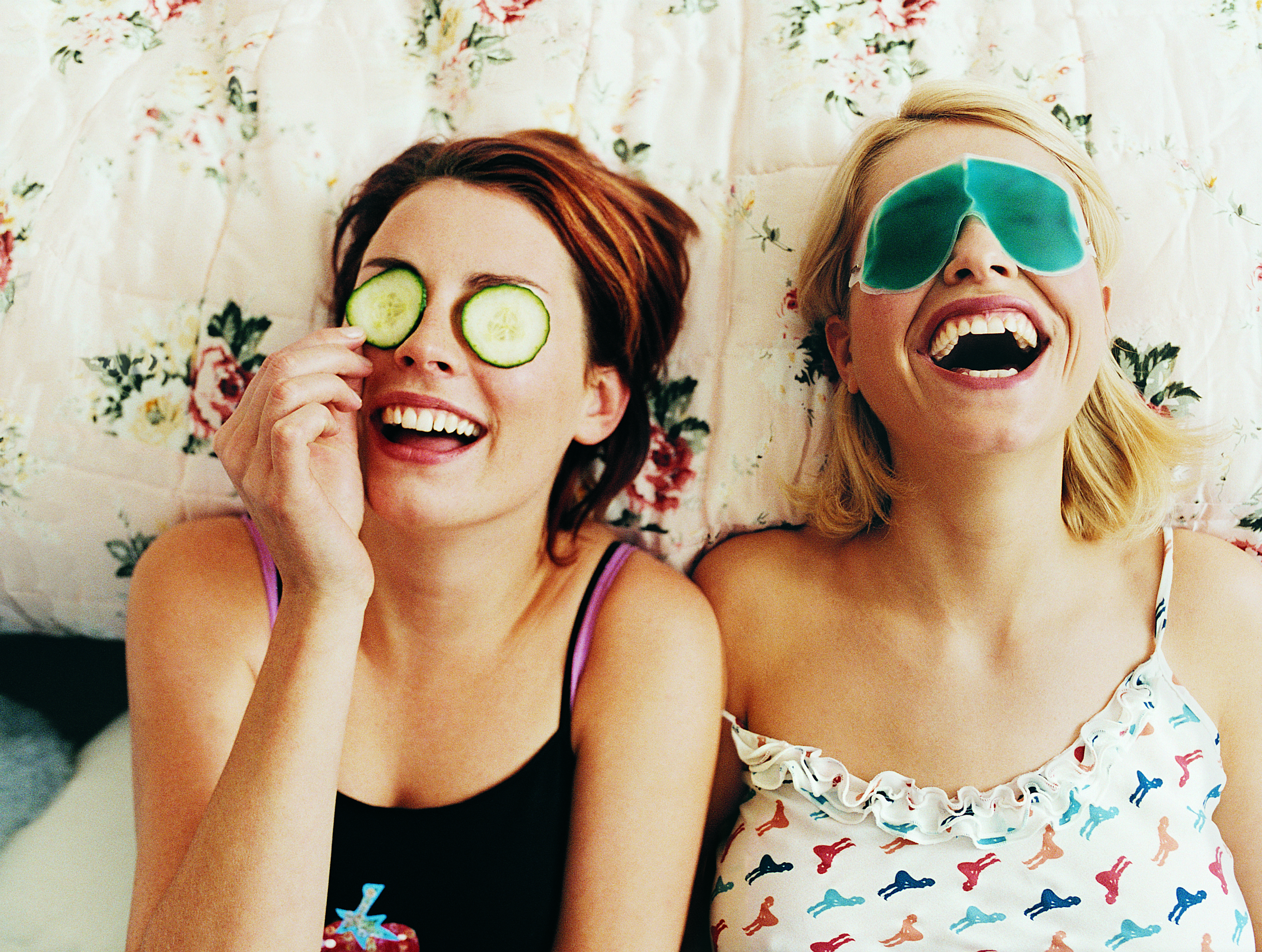 Two women with DIY face masks lying down and laughing