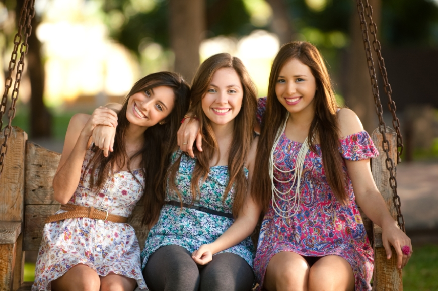 Three happy teenage girls sitting on swing chair