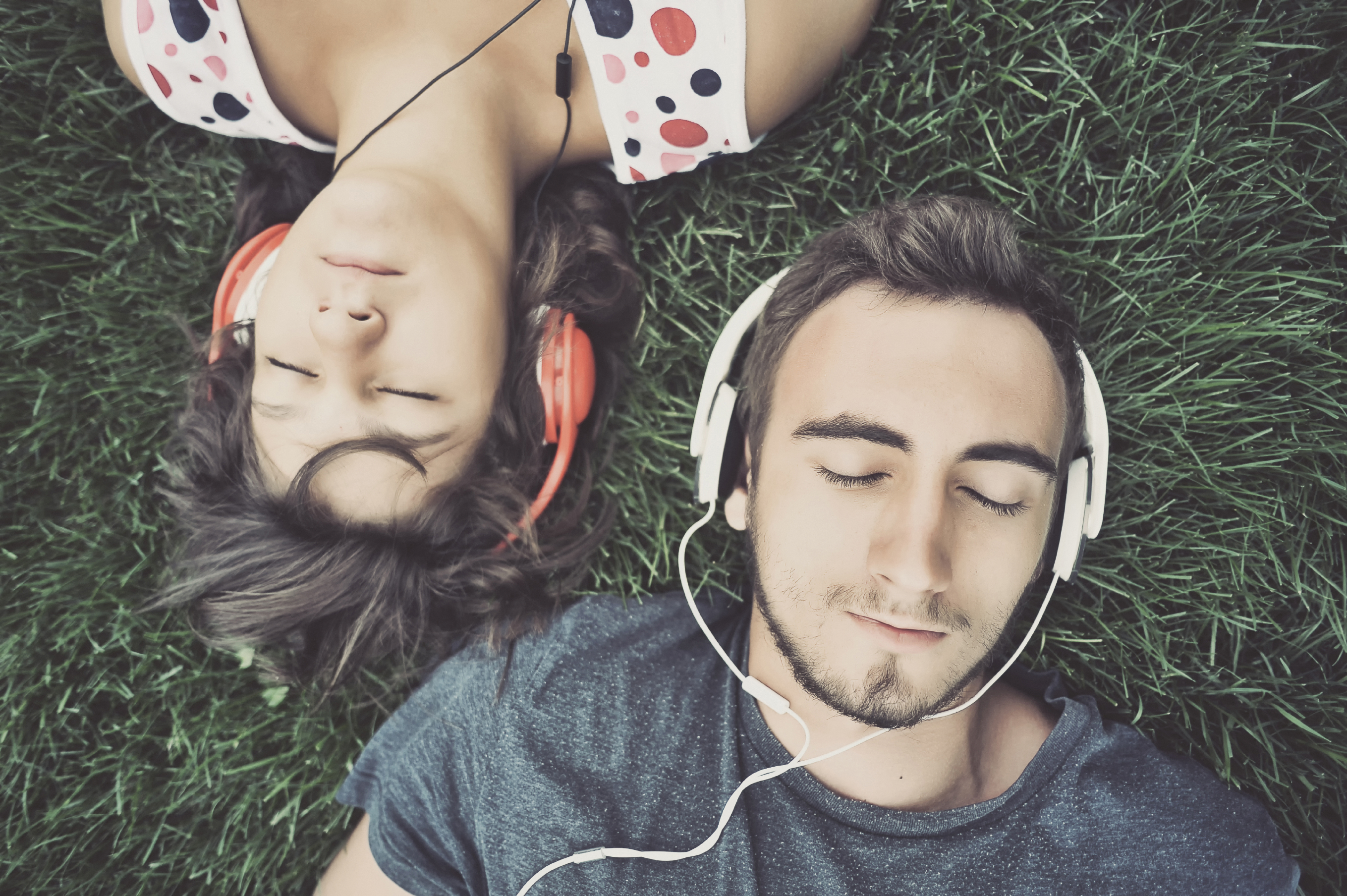 Couple listening to music whilst lying on grass