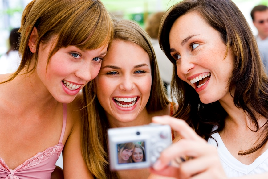3 female friends smiling and talking a selfie to capture the moment. camera