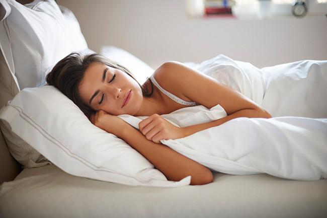 Woman sleeping in white linen