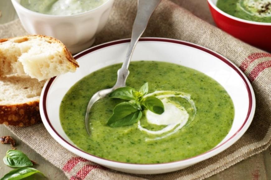 broccoli, spinach and potato soup in white bowl with bread