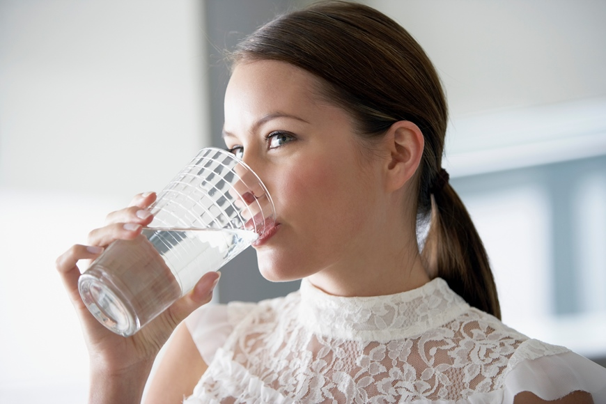 Woman drinking water from a clear glass